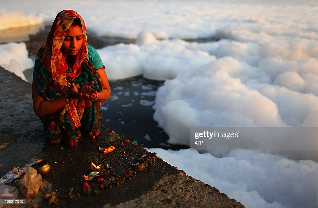 An Indian Hindu devotee prays near polluted foam in the Yamuna river in New Delhi at dawn on December 9, 2012. India's Supreme Court said on December 8, all parameters of water quality of river Yamuna indicate that it resembles a drain and urged authorities to make it pollution-free. Over 2,400 million liters of untreated sewage flows into the Yamuna every day. AFP PHOTO/ Andrew Caballero-Reynolds