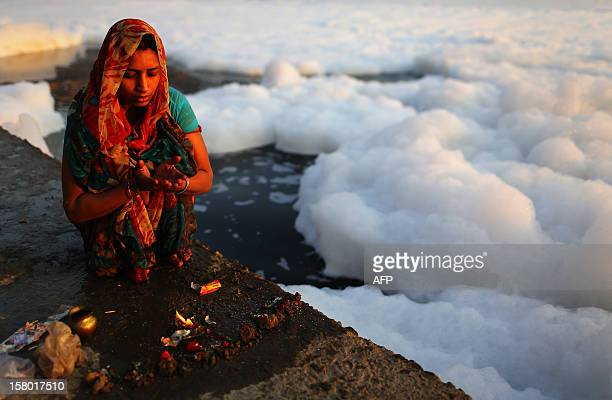 An Indian Hindu devotee prays near polluted foam in the Yamuna river in New Delhi at dawn on December 9 2012 India's Supreme Court said on December 8...