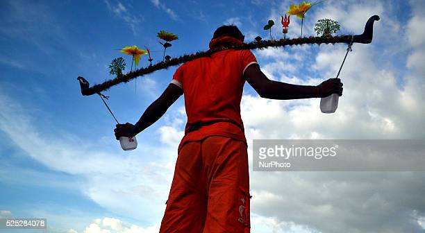 An Indian hindu devotee prepare for his Kanwar yatra as kanwariyas take holy water of River Ganga in plastic containors on the sacred month of...