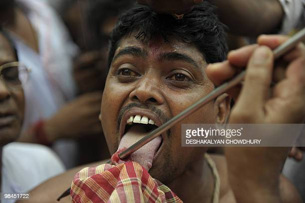 An Indian Hindu devotee reacts as a priest pierces his tongue with a metal rod during the ritual of Shiva Gajan at a village in Bainan some 80 kms...