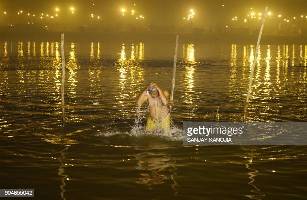 TOPSHOT An Indian Hindu devotee takes a holy dip during the Makar Sankranti festival during the annual Magh Mela gathering at Sangam the confluence...