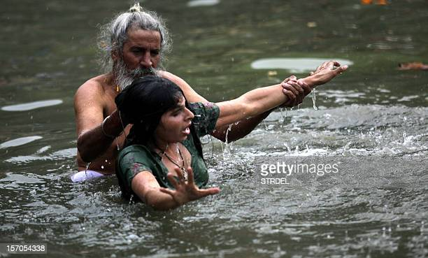 An Indian Hindu devotee undergoes a ritualistic bath during the annual farmers fair at Shama Chak Jhiri some 22kms from Jammu on November 28 2012...