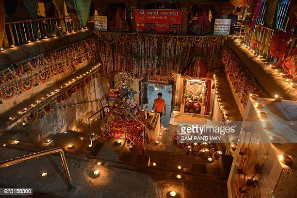 TOPSHOT An Indian Hindu devotee walks amidst the oil lit lamps on the occasion of Dev Diwali at Matar Bhavani Vav in Asarwa area of Ahmedabad on...