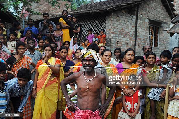 An Indian Hindu devotee with his tongue pierced by a metal rod stands in front of a crowd of people during the ritual of Shiva Gajan at a village in...