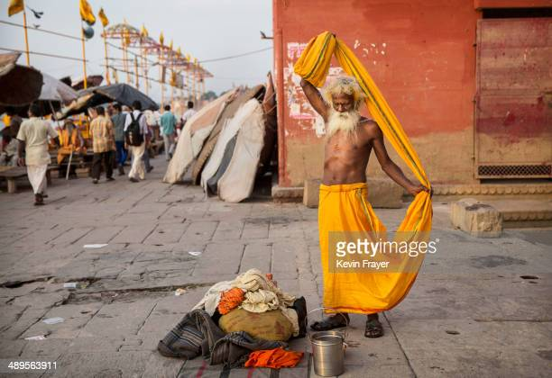 An Indian Hindu holy man or Sadhu puts on his clothing on May 11 2014 on the Ganges River in Varanasi India Indians will vote in the ninth and final...