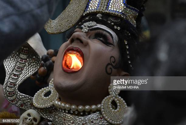 TOPSHOT An Indian Hindu man dressed as Lord Shiva holds a lit candle in his mouth as he takes part in a religious procession ahead of the Maha...
