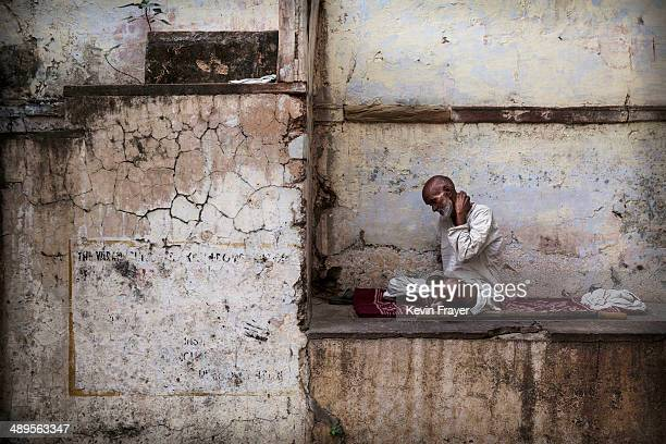 An Indian Hindu man sits in an alleyway on May 11 2014 in Varanasi India Indians will vote in the ninth and final phase of a general election Monday...