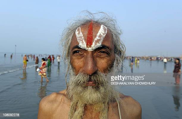 An Indian Hindu pilgrim looks towards the sun as he peforms a ritual at the Gangasagar some 180 Kms south of Kolkata on early January 15 2011 on the...