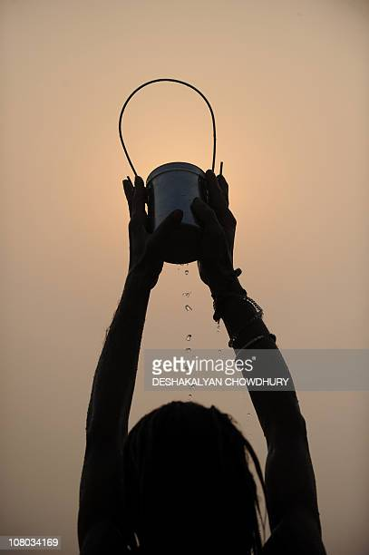 An Indian Hindu pilgrim performs rituals after taking a dip in the Gangasagar some 180 Kms south of Kolkata on early January 14 2011 during the hold...