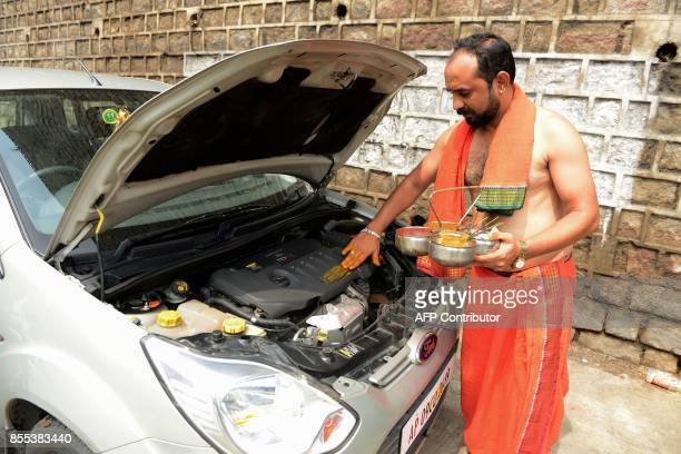 An Indian Hindu priest performs an Ayudha Puja ritual on a car for the DussehraVijaya Dashami festival in front of a temple in Hyderabad on September...