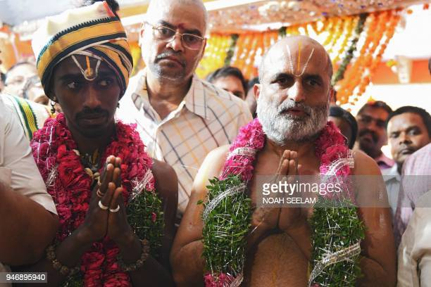 An Indian Hindu priest CS Rangarajan performs rituals along with a Dalit devotee Aditya Parasri after carrying him on his shoulders into the sanctum...