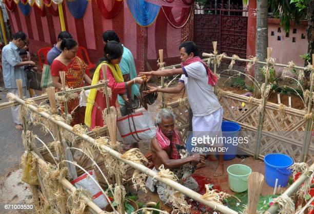 An Indian Hindu priest sacrifices a chicken during a ritual at the altar of the tribal deity 'Garia' during the Garia Puja festival in Agartala the...