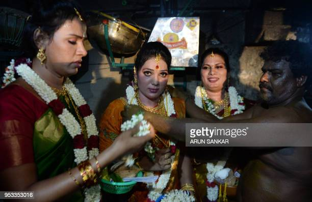 An Indian Hindu priest ties a 'thali' around the neck of a member of the transgender community during a ritual signifying marriage to the Hindu...