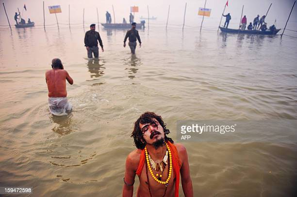 An Indian Hindu Sadhu or Holy Man closes his eyes as he prays while bathing in the Sangham or the confluence of the the Yamuna and Ganges rivers...