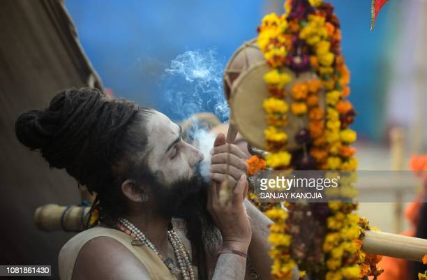An Indian Hindu Sadhu sits outside his tent as he smokes ahead of the Kumbh Mela festival in Allahabad on January 13, 2019. - The festival attracts...
