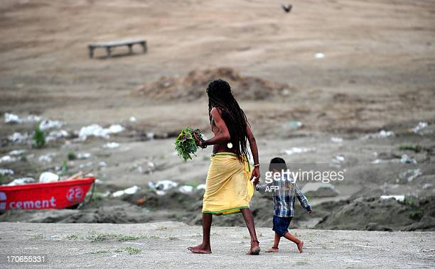 An Indian Hindu Sadhu walks with his adopted child Bajrangi on the banks of the Sangam on father's day in Allahabad on June 16 2013 AFP PHOTO /...