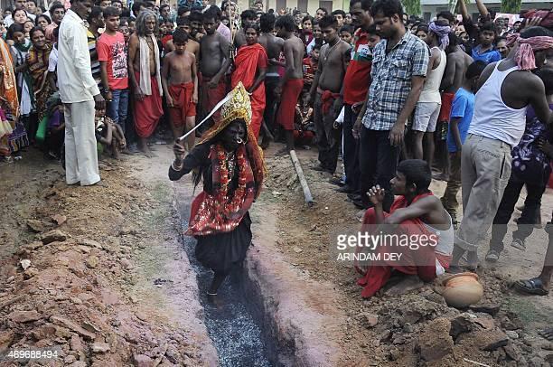 An Indian Hindu woman devotee dressed as goddess Kali runs over smouldering charcoal during the ritual of Shiva Gajan at Pratapgarh village in...