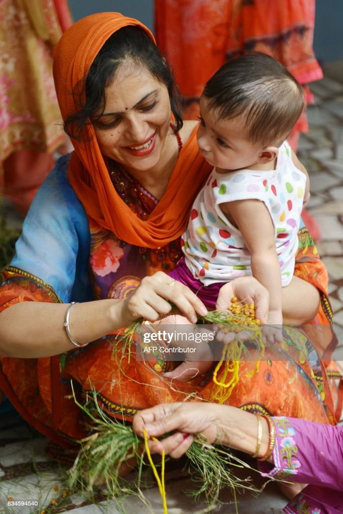 An Indian Hindu woman holds her son as she offers a ritual prayer during the traditional `Gai Bachra Puja ` at a temple in Amritsar on August 18 2017.