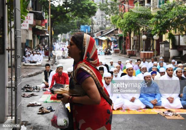 An Indian Hindu woman offers prayers by a temple as Indian Muslims offer Eid alFitr prayers in Kolkata on June 26 2017 Muslims around the world are...