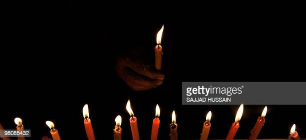 An Indian holds a candles during an Earth Hour campaign in Mumbai on March 27 2010 Dozens of Indians lit candles to observe Earth Hour and called for...