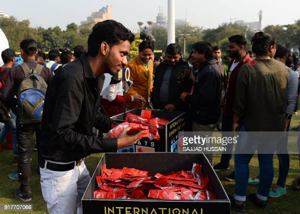 An Indian holds condoms as he poses for photographs during an event to mark International Condom Day in New Delhi on February 13, 2018. The event was...