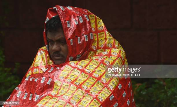 An Indian homeless covers himself with a plastic sheet during heavy rain in Mumbai on December 5 2017 Cyclone Ockhi brought heavy rain to Mumbai as...