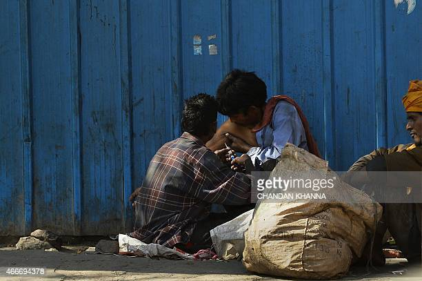 An Indian homeless man uses a syringe to inject drugs into the arm of an addict on the streets of New Delhi on March 18, 2015. AFP PHOTO / CHANDAN...