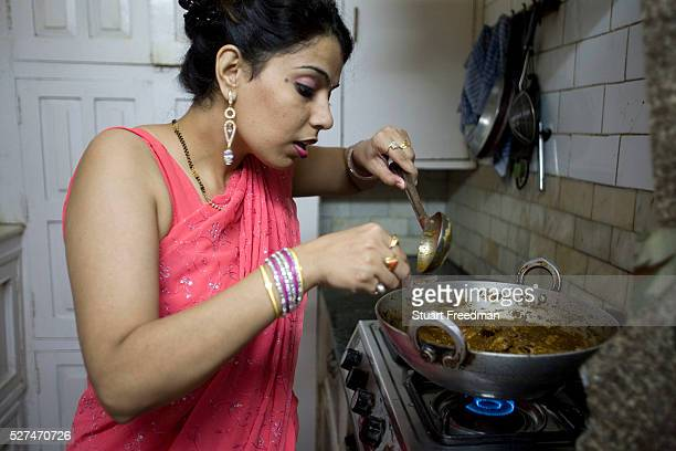 An Indian housewife at home in New Delhi cooks her favourite dish in her kitchen New Delhi India