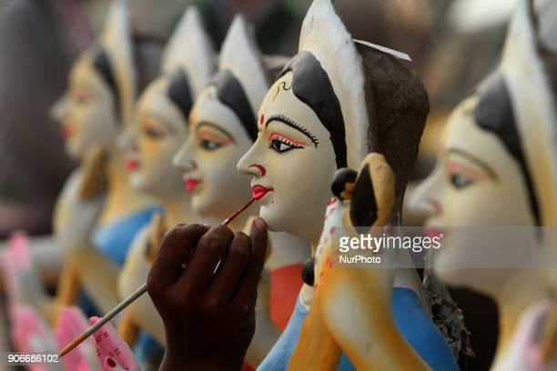 An Indian image maker applying colors into the clay idols of Goddess Saraswati at his workshop before supply it to the market for sale ahead of the...