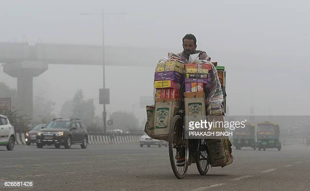 An Indian incense stick supplier transports his stock on a bicycle on a cold foggy morning in New Delhi on November 30 2016 / AFP / PRAKASH SINGH