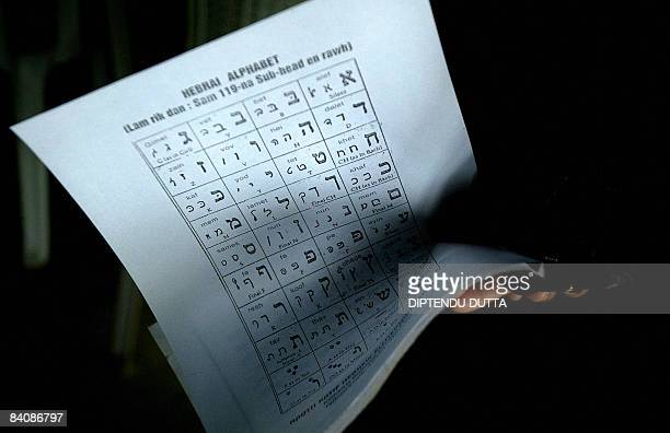 An Indian Jew holds a sheet with letters of the Hebrew alphabet while taking part in a class at Hebrew learning centre set up in a synagogue in...