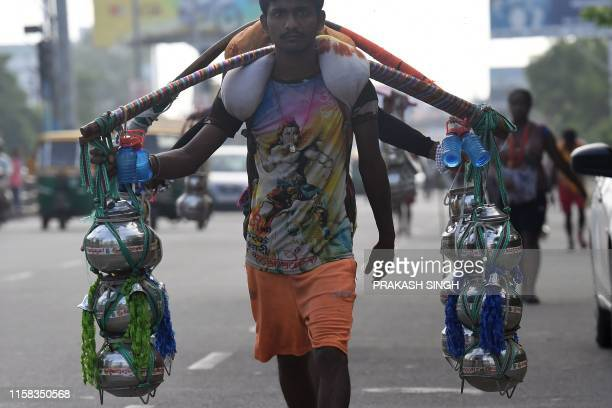 TOPSHOT An Indian Kanwariya a Hindu devotee of the Hindu deity Shiva carries pots of holy water from the Ganges river on his return journey from...