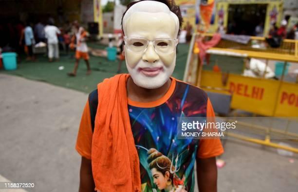 An Indian Kanwariya a Hindu devotee of the Hindu deity Shiva wears a mask of Indian Prime Minister Narendra Modi as he takes a break on his return...