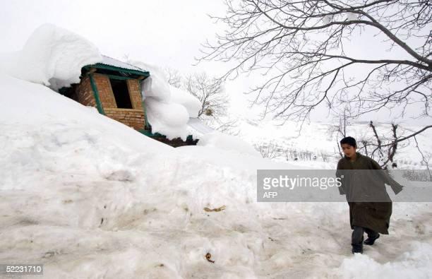 An Indian Kashmiri child survivor walks past a house devastated by an avalanche at Waltingo Nar 90 kilometers south of Srinagar 23 February 2005...