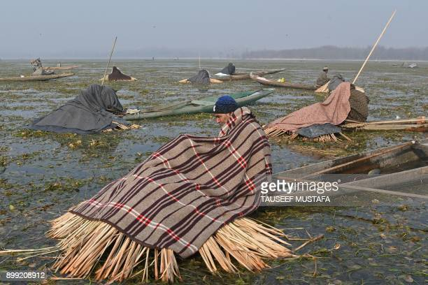 An Indian Kashmiri fisherman takes a break between catching fish with a harpoon in Anchar Lake on the outskirts of Srinagar on December 28 2017 The...