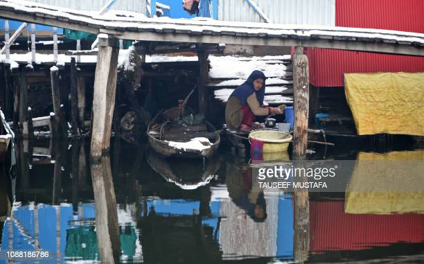 An Indian Kashmiri girl washes utensils under a snowcovered foot bridge after snowfall in the interiors of Dal Lake in Srinagar on January 25 2019