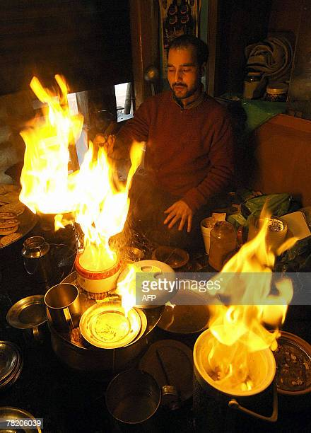An Indian Kashmiri man Aijaz Ahmed pours hot cooking oil on a plate containing a meat dish locally known as 'Harisa' before serving it to his...