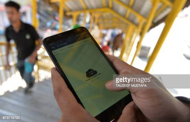 An Indian Kashmiri man browses blocked services on the internet on his mobile phone on a footbridge in Srinagar on April 27 2017 Authorities in...