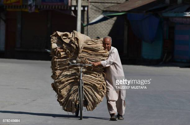 TOPSHOT An Indian Kashmiri man carries sacks on his bicycle on the 13th day of a curfew in Srinagar on July 21 2016 Residents in Indianadministered...