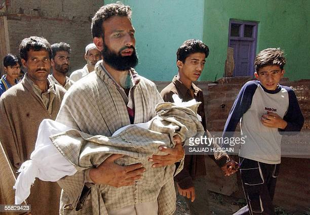 An Indian Kashmiri man carries towards the city graveyard the body of one and a half-year-old girl Balgees, killed along more than 40 others in a...