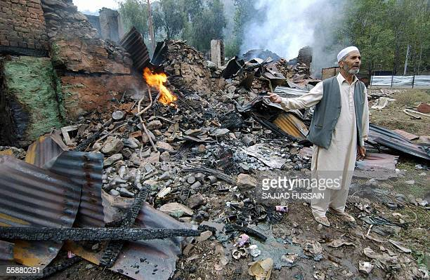 An Indian Kashmiri man stands amid debris of burnt shops following a powerful earthquake measuring at least 76 on the Richter scale in Uri some 100...