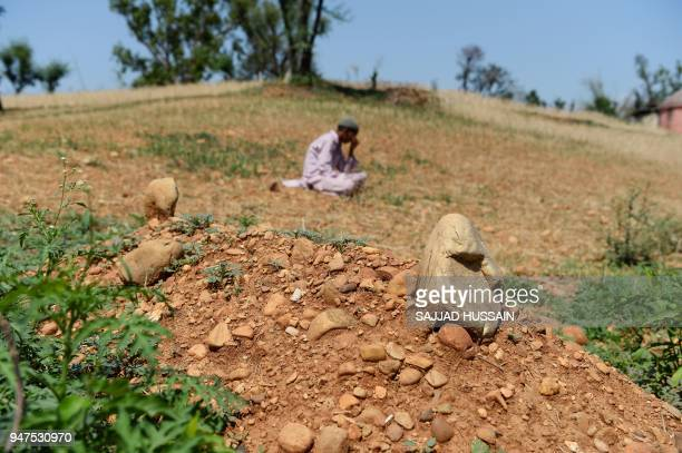 An Indian Kashmiri nomad boy sits near the grave of the eightyearold girl who was raped and murdered at Koota Khanna village in Kathua district of...