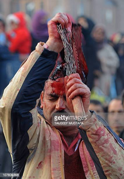An Indian Kashmiri Shiite Muslim flagellates himself with a cluster of knives during a religious procession in Srinagar on December 14 2010 held on...