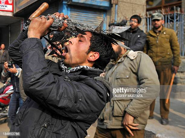 An Indian Kashmiri Shiite Muslim man flagellates himself with knives during a rally in the centre of the city to commemorate the martyrdom of Imam...