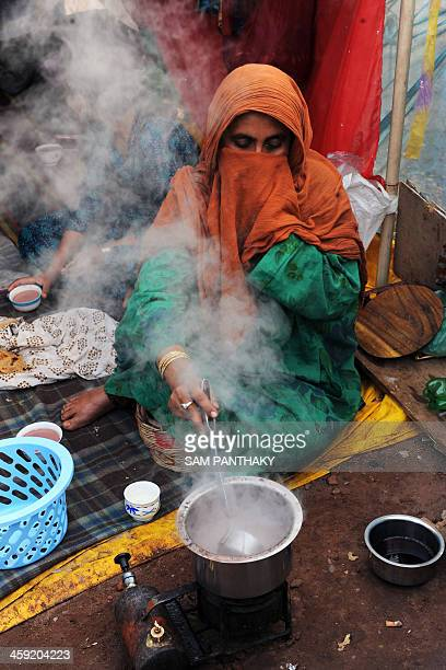 An Indian Kashmiri woman living in Gujarat state prepares tea at a makeshift tent during cold weather in Ahmedabad on December 24 2013 Mainly dry...