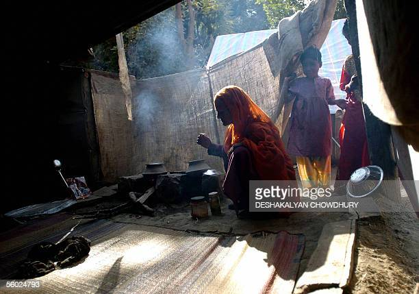 An Indian Kashmiri woman prepares food inside a temporary shelter at Bhukari near the Line of Control some 225 kms northwest of Srinagar 28 October...