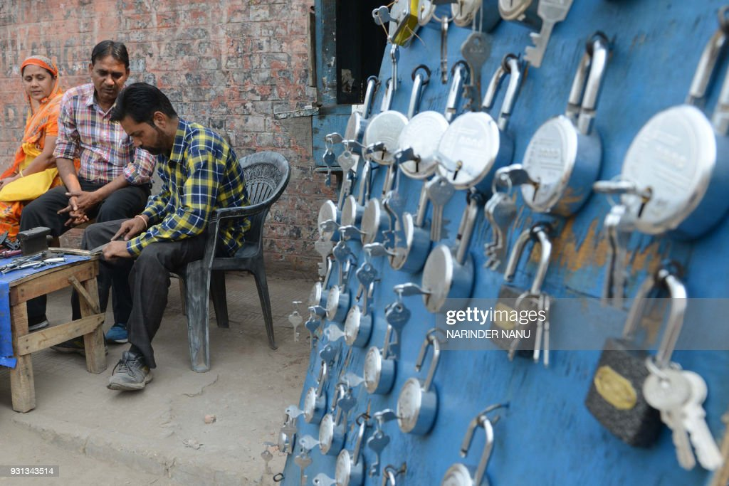 An Indian key maker crafts a duplicate key at a roadside stall in Amritsar on March 13 2018 / AFP PHOTO / NARINDER NANU