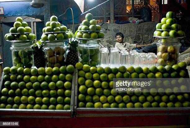An Indian kid is seen behind a stall offering orange juice in New Delhi on June 19, 2009. India's annual inflation rate slipped into negative...