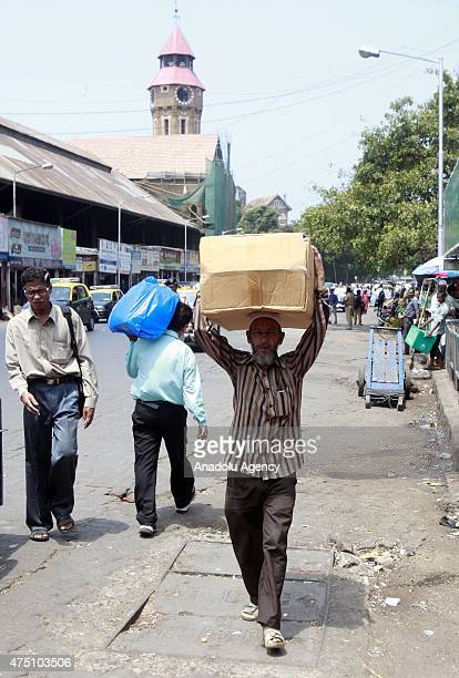 An indian laborer carries a box on his head at a hot day in Mumbai on May 29, 2015. At least 1400 people have died in a major heatwave that has swept...