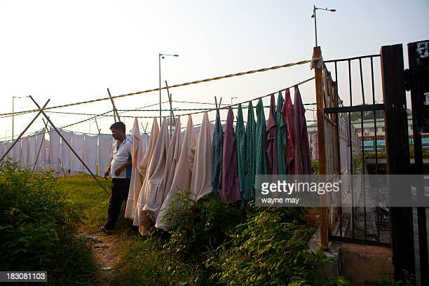 CONTENT] An Indian laborer from a guest house prepares to dry bed covers at an outside drying area near the highway in the old part of the city